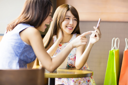 happy young woman looking at phone in coffee shop