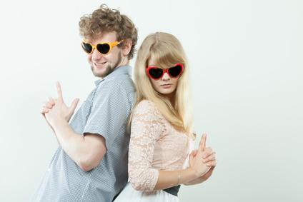 Couple man and woman making gun gesture.