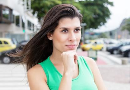 Vertrumte Frau im grnen Shirt in der Stadt