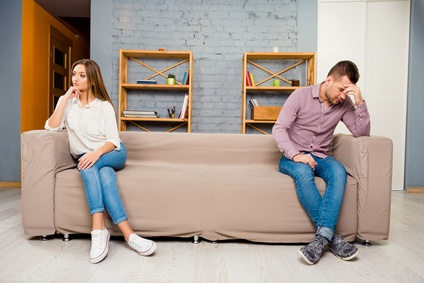 Man and woman sitting separate on couch after quarrel
