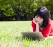attractive asian woman using laptop in the park