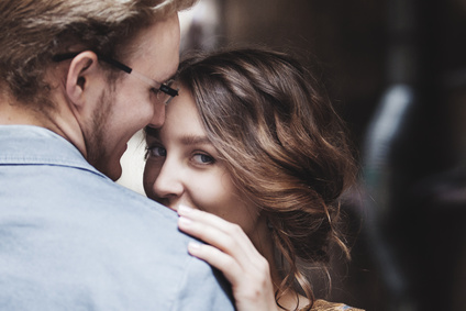 Young couple in love outdoor.  Man hugs  woman. The girl looks over the shoulder of a partner