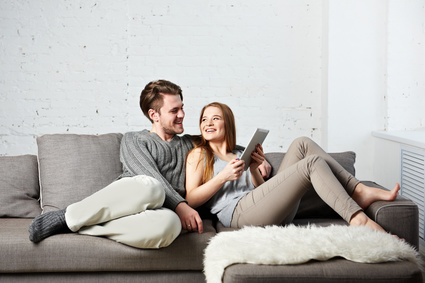 Romantic relaxed young couple using tablet computer on sofa