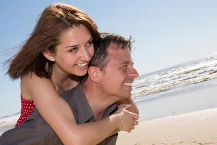 Love - Happy couple on beach having fun piggyback ride