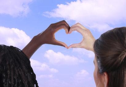 Afrikanerin und Europerin halten die Hnde zu einem Herz zusammen vor blauem Himmel mit Wolken