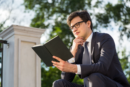 Thoughtful businessman reading book outside