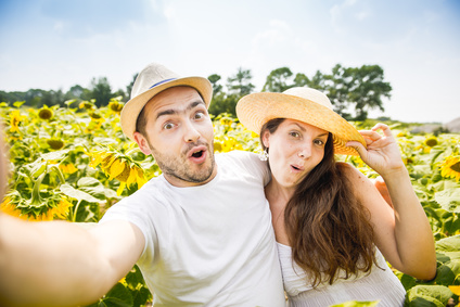 young happy couple man and woman are in a field of sunflowers, make selfie pics